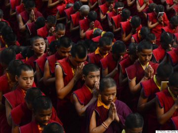 Nepalese novice Buddhist monks living at the Bodhgaya Tergar monastary offer prayers for the victims of an earthquake in Nepal at the Bodhgaya Mahabodhi temple in the Indian town of Bodhgaya on April 26, 2015. Powerful aftershocks rocked Nepal April 26, 2015, panicking survivors of a quake that killed more than 2,300 and triggering fresh avalanches at Everest base camp, as rescuers dug through rubble in the devastated capital Kathmandu. Terrified residents, many forced to camp out in the capital after the April 25, 2015, quake reduced buildings to rubble, were jolted by a 6.7-magnitude aftershock that compounded the worst disaster to hit the impoverished Himalayan nation in more than 80 years. AFP PHOTO / STR        (Photo credit should read STRDEL/AFP/Getty Images)