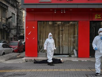 EDITORS NOTE: Graphic content / This photo taken on January 30, 2020 shows officials in protective suits checking on an elderly man wearing a facemask who collapsed and died on a street near a hospital in Wuhan. - AFP journalists saw the body on January 30, not long before an emergency vehicle arrived carrying police and medical staff in full-body protective suits. The World Health Organization declared a global emergency over the new coronavirus, as China reported on January 31 the death toll had climbed to 213 with nearly 10,000 infections. (Photo by Hector RETAMAL / AFP) / TO GO WITH China-health-virus-death,SCENE by Leo RAMIREZ and Sebastien RICCI